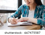 Stock photo elegant smart woman writing down her ideas 667475587
