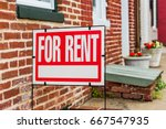 Small photo of Rent sign closeup against brick building