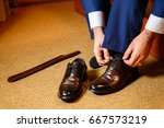 the groom wears his shoes | Shutterstock . vector #667573219