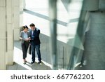 coworkers discussing documents... | Shutterstock . vector #667762201