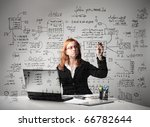 Businesswoman sitting at a desk in front of a laptop and drawing some schemes - stock photo
