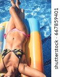 Small photo of Crop fit girl on colorful air mattress floating in water of pool enjoying sunlight.