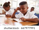 elementary school boy reading a ... | Shutterstock . vector #667977991
