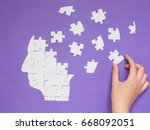 Small photo of Female hand trying to connect pieces of white jigsaw puzzle as a human head brain on purple background. Creative idea for solving problem, memory loss, mental health or psychosis treatment concept.