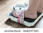 feet tied up with measuring... | Shutterstock . vector #668247181