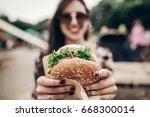 big juicy burger in hand.... | Shutterstock . vector #668300014