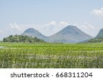 bush and mountains in lake... | Shutterstock . vector #668311204