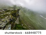 edge of steep slope on rocky hillside in foggy weather. dramatic scenery in mountains - stock photo