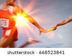 athletes passing relay baton | Shutterstock . vector #668523841