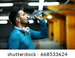 young athlete man is drinking... | Shutterstock . vector #668533624