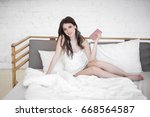 young beautiful woman in bed... | Shutterstock . vector #668564587