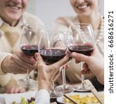 Small photo of Happy family toasting granparents anniversary holding glasses with wine, smiling