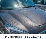 Small photo of Dented car after a big hail storm