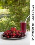 Small photo of A house hamper of cherries, strawberries and raspberries in a glass. Plate with fresh fruit. Summer refreshing drink on a green background
