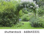 Stock photo english cottage garden with white rose arch entrance and colorful summer flowers in bloom 668643331