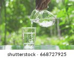female hand pouring water from... | Shutterstock . vector #668727925