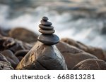 stones pyramid on pebble beach... | Shutterstock . vector #668813281