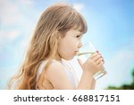 the child holds a glass of... | Shutterstock . vector #668817151