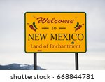 Small photo of welcome to new mexico sign. yellow state sign on highway road. land of enchantment.