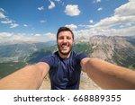 hiker at the top of a pass... | Shutterstock . vector #668889355