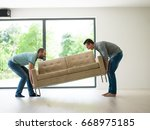 two young men carry the sofa in ... | Shutterstock . vector #668975185