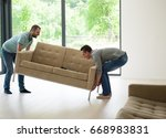 two young men carry the sofa in ... | Shutterstock . vector #668983831