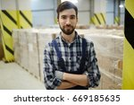 young storehouse worker looking ... | Shutterstock . vector #669185635