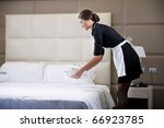 Stock photo maid making bed in hotel room 66923785