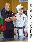 Small photo of BERLIN - MARCH 18, 2017: Unflappable coach before the fight. European championship Kyokushin World Union (KWU) for Children and Youth.