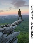 Man standing high on tip of rock at Rough Ridge Overlook on Grandfather Mountain in North Carolina.