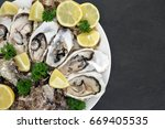 Small photo of Oyster aphrodisiac food on a porcelain plate with lemon fruit and parsley herb on slate background.