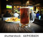 Stock photo nachos and beer on a table of a sports bar 669438604