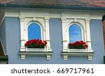 Small photo of gothic windows with white ornaments and red gerania at an old house, blue sky reflecting in the window glass