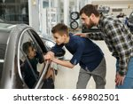 Small photo of Shot of a young boy talking to his cheerful father sitting together in a new car driving travelling trip journey happiness lifestyle parent vehicle automobile rent safety insurance family parenting