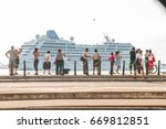 "Small photo of HAVANA - MAY 2 2016 - Cuban people watch the docking maneuvers of ""Adonia"", first american cruiser to visit Cuba in five decades."