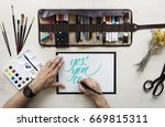 top view on calligrapher hands... | Shutterstock . vector #669815311