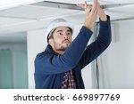 worker installing board ceiling | Shutterstock . vector #669897769