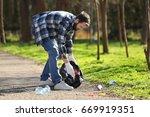 young volunteer picking up... | Shutterstock . vector #669919351