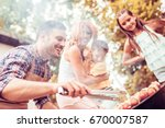 happy family having a barbecue... | Shutterstock . vector #670007587