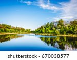 Summer lake near the forest with trees. - stock photo