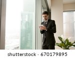 Small photo of Serious businessman holding tablet standing near big office window, using business apps for organizing meetings, making payments, planning daily tasks, reading news, monitoring realtime market data