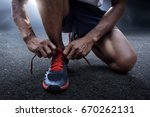 man tying running shoes | Shutterstock . vector #670262131