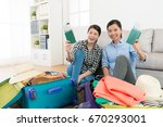 Small photo of cheerful pretty sisters packing travel clothing luggage suitcase at home and face to camera showing passport with boarding card.