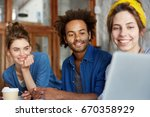 Small photo of Portrait of three students of different races sitting at table looking at laptop making video call abroad using free internet connection speaking with their friend having good mood and smiling broadly