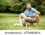 Man and his dog as friends together at the garden in summer - stock photo