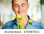 handsome man smelling flowers | Shutterstock . vector #670487011