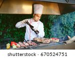 the chef prepares meat on the... | Shutterstock . vector #670524751
