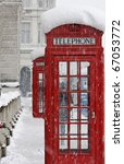 Red telephone box in snow - stock photo