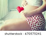 beautiful pregnant woman at home | Shutterstock . vector #670575241
