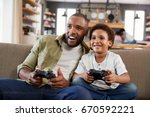 father and son sitting on sofa... | Shutterstock . vector #670592221
